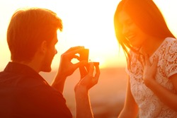 Successful marriage proposal at sunset. Man offering engagement ring to his glad girlfriend