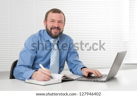 successful mature business man smiling and working on laptop