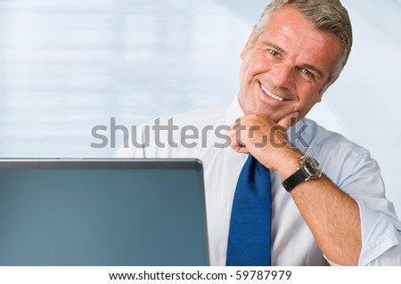 Successful mature businessman looking at camera behind his laptop at work in office