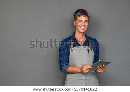 Successful mature woman in apron standing against grey wall. Happy small business owner holding tablet and looking at camera. Smiling portrait of entrepreneur standing satisfied with copy space.