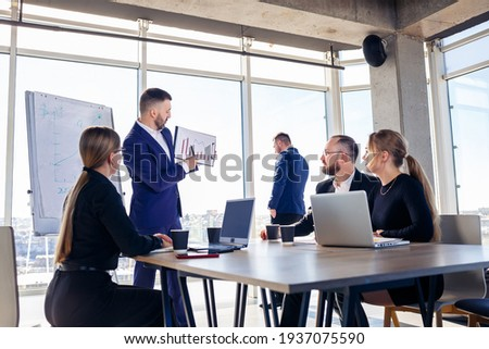 Successful meeting of business people, discussing new business ideas, using diagrams, sitting together. Modern office background. Meeting of business partners at the conference on business development