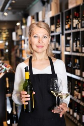 Successful middle aged woman owner of winery inviting to tasting wine of own production ..
