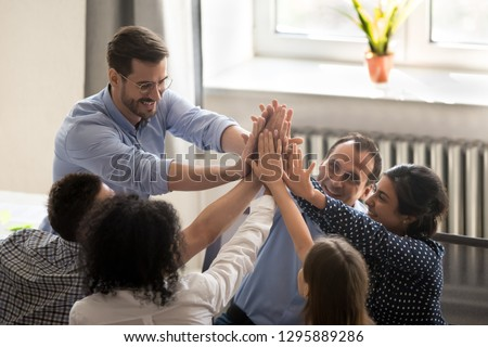 Successful millennial coworkers rises hands giving high five congratulating each other with great deal or goal achievement. Diverse multiracial business people feel happy received good news or reward