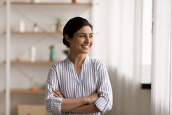 Successful millennial indian lady stand at home keep arms crossed on chest look at window with confident smile. Happy mixed race female private enterpreneur proud of being self made business woman