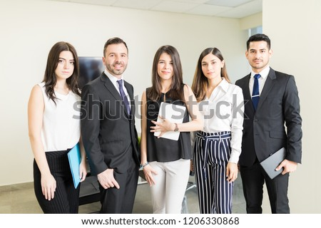 Successful multiethnic marketing team standing together in office