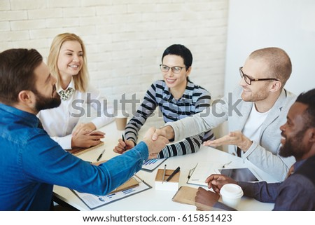 Successful negotiations with business partner: two young bearded men shaking hands and smiling during meeting, waist-up portrait #615851423