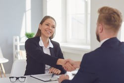 Successful office interview. The conclusion of the contract. Businessman and businesswoman handshake at the table after meeting.