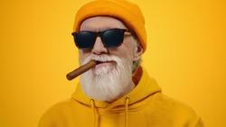 Successful old man smoking inside. Aged senior guy savoring taste of cigar on yellow studio background. Satisfied elderly male person relaxing indoors.