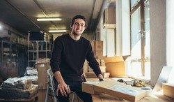 Successful online business owner sitting at his workdesk. Young man with laptop and shipment box on desk, looking at camera and smiling.