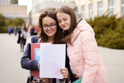 Successful passing of important examination. Happy female student with a friend looking to the test sheet with excellent A grade result