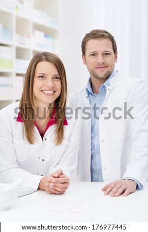 Successful pharmacy partnership with a confident young male and female pharmacist standing close together behind the counter in the pharmacy smiling at the camera