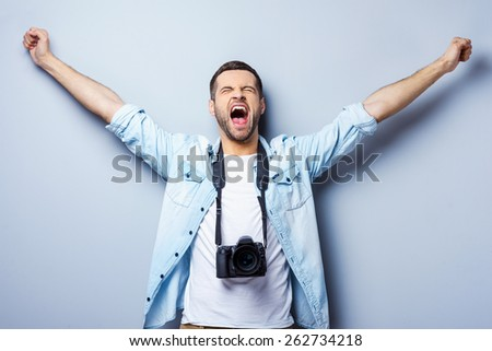 Successful photographer. Happy young man with digital camera keeping arms raised and eyes closed while standing against grey background #262734218
