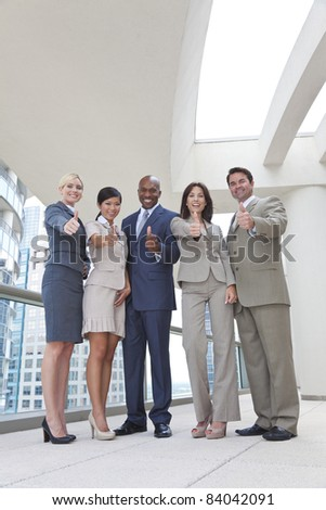 Successful positive interracial group of business men & women, businessmen and businesswomen team, giving thumbs up