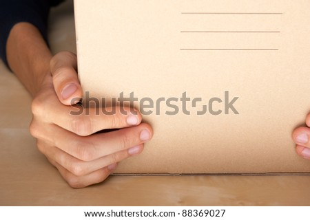 Successful Postal or delivery service concept. Man holding cardboard box with two arms on table