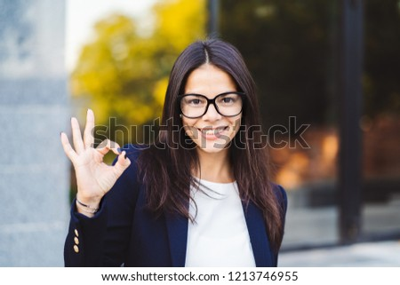 Successful pretty woman look to camera and showing OK sign on office building background. Professional female manager wearing glasses and suit. Student girl.