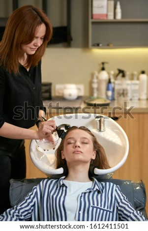 successful professional hairdo doing modern stylish hair for young beautiful lady using equipment, washing hair for future colours