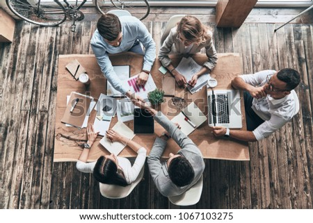 Successful professionals. Top view of young modern men in smart casual wear shaking hands while working with their colleagues in the creative office #1067103275
