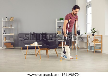 Successful rehabilitation and recovery of people after physical injury such as bone fracture in car or home accident: Young man with broken leg trying to walk with crutches and making good progress Stock photo ©