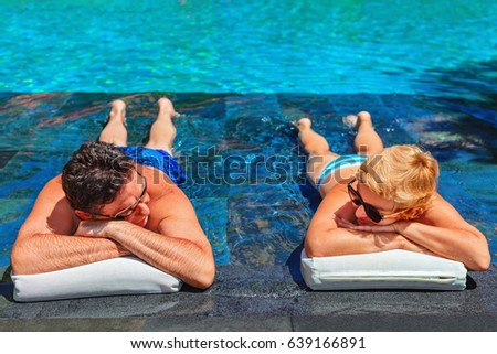 Successful retirement recreation, summer vacation concept. Retired mature couple enjoying beautiful sunny day in swimming pool at beach club. Happy senior woman and man lying in water at poolside.