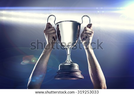 Successful rugby player holding trophy against spotlights #319253033