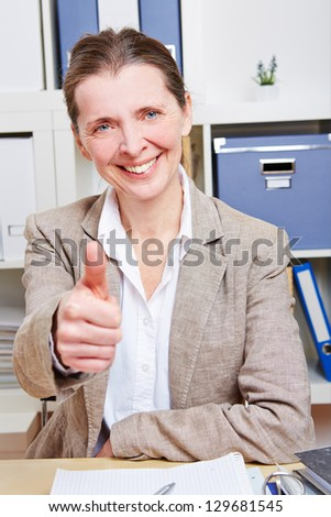 Successful senior business woman in her office holding her thumb up