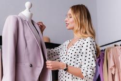 successful showroom proprietor touching stylish blazer on mannequin