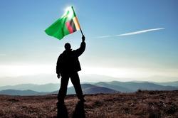 Successful silhouette man winner waving Zambia flag on top of the mountain peak