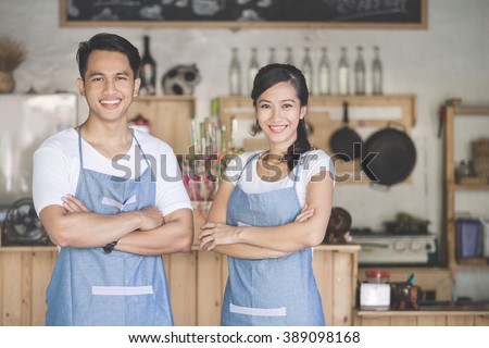 Successful small business owner proudly standing in front of their cafe