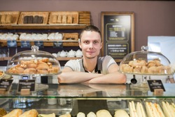 Successful small business owner standing behind the counter and smiles with employee in bakery background
