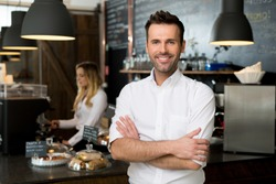 Successful small business owner standing with crossed arms with employee in background preparing coffee