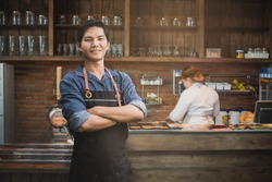 Successful small business owner standing with crossed arms with employee in background preparing coffee. Portrait of asian young male cafe owner .