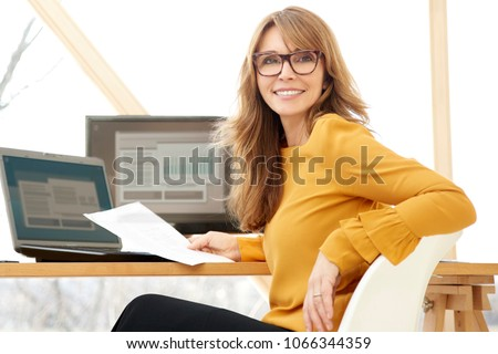 Successful smiling mature businesswoman using laptop and computer while doing some paperwork at the office.