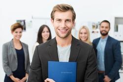 Successful smiling young male job applicant holding a blue file with his curriculum vitae posing in front of his new work colleagues or business team