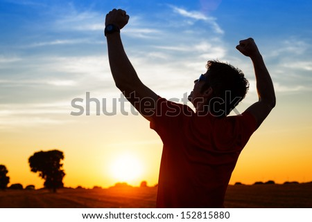 Successful Sportsman Raising Arms On Golden Sky Back Lighting Sunset Summer After Cross Running. Fitness Male Athlete With Arms Up Celebrating Goals After Sport Exercising And Working Out Outdoors.