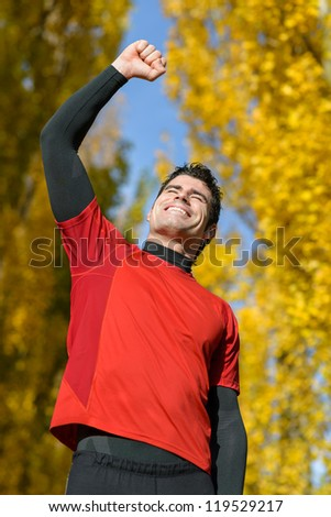 Successful sportsman winning. Male Happy athlete raising arm celebrating achievement on autumn.