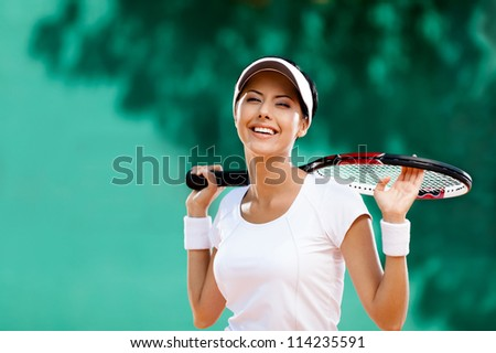 Successful sportswoman with racket at the tennis court. Healthy lifestyle