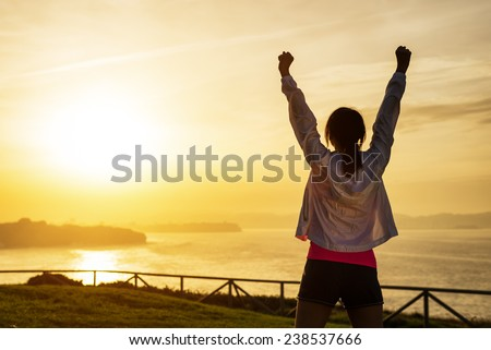 Successful sporty woman raising arms towards golden beautiful sunset and sea. Female athlete celebrating sport success and goals. Healthy lifestyle and freedom concept.
