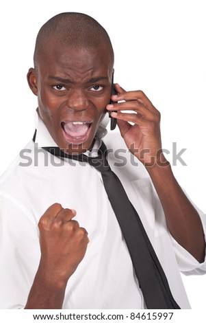 Successful surprised young handsome businessman with clenched fist using mobile phone