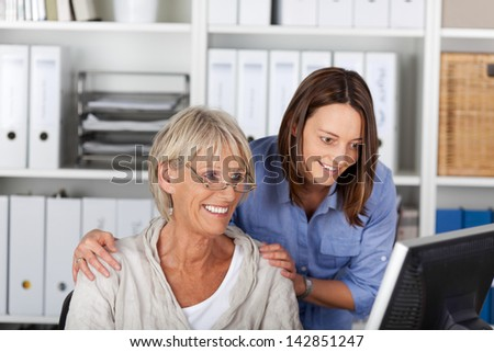 Successful team at the office consisting of an elderly and young woman standing arm in arm studying a desktop monitor with smiles of anticipation