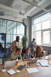 Successful team in coworking space. Vertical shot of multiracial coworkers communicating, sharing fresh ideas while working together in the modern office