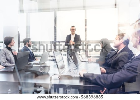Successful team leader and business owner leading informal in-house business meeting. Business people working on laptops in foreground and glass reflections. Business and entrepreneurship concept. #568396885