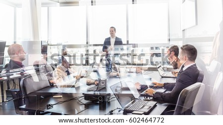 Successful team leader and business owner leading informal in-house business meeting. Business people working on laptops in foreground and glass reflections. Business and entrepreneurship concept. #602464772