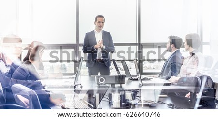 Successful team leader and business owner leading informal in-house business meeting. Business people working on laptops in foreground and glass reflections. Business and entrepreneurship concept. #626640746
