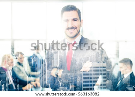 Successful team leader and business owner proudly standing with arms crossed in front of office window with New York city panorama reflection in glass. Employees working at office in background. #563163082