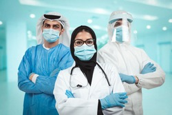 Successful team of Arabic medical doctors are looking at camera while standing in hospital with arms crossed male and female doctors in protective gear fighting coronavirus COVID-19.