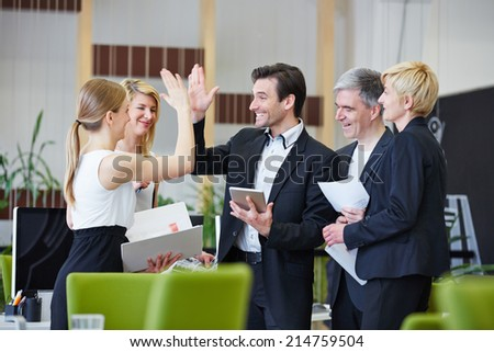 Successful team of business people giving high five in the office #214759504