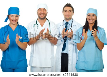 Successful team of four different doctors applauding together isolated on white background