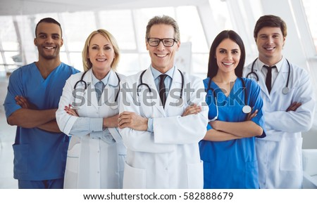 Successful team of medical doctors are looking at camera and smiling while standing in hospital