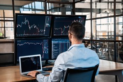 Successful trader working in modern office, looking at display, sale and buy bitcoin and analyzing index on cryptocurrency market diagram