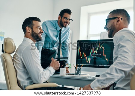 Successful traders. Group of young modern men in formalwear analyzing stock market data while working in the office